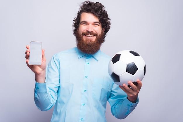 Regardez cette application incroyable, un homme barbu joyeux en mode décontracté montrant un téléphone à écran et tenant un ballon de football