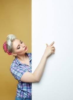 Regardez cette bannière. une belle blonde souriante se tient derrière la bannière et pointe du doigt.