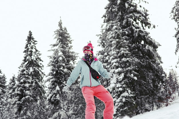 Regardez d'en bas à la femme en costume rose descendant sur le snowboard le long de la ligne forestière