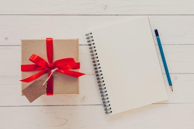 Regardez ci-dessus boîte cadeau et cahier avec étiquette sur fond en bois avec space.vintage boîte cadeau avec étiquette sur fond en bois. ensemble brun sur un pont.