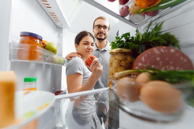 Regardez dans le frigo. jeune et réussi couple amoureux regarde dans le frigo et sort du frigo une bouteille de lait en se tenant debout dans la cuisine et prépare le petit déjeuner.