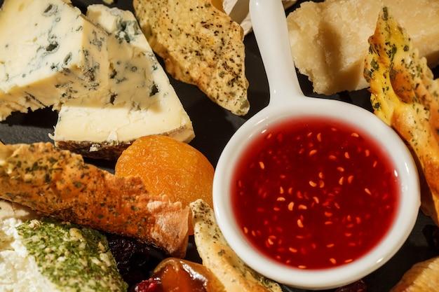 Regardez depuis le dessus au bol avec la sauce aux canneberges entre des morceaux de fromage sur une assiette noire