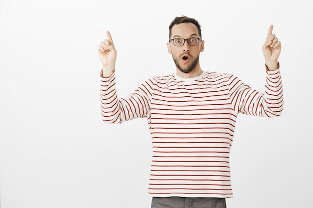 Regardez, c'est incroyable. portrait de bel homme européen excité impressionné avec des soies dans des verres