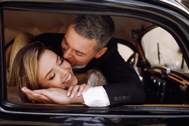 Regardez de l'extérieur l'adorable couple en robe de mariée