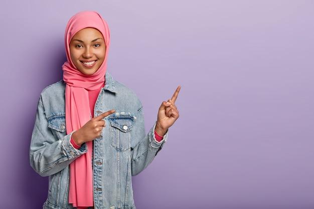 Regardez de cette façon. heureuse belle femme arabe qui pointe à droite