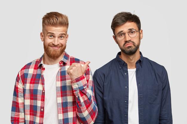 Regardez ce gars! un jeune homme barbu au gingembre montre du pouce son camarade qui a une expression hésitante