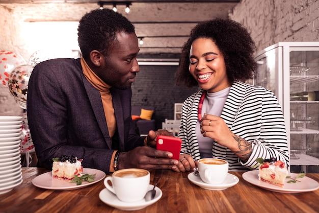 Regardez là. homme joyeux positif tenant un smartphone dans sa main tout en montrant une photo à sa petite amie