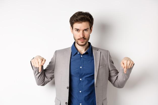 Regardez ici. bel homme barbu en costume pointant les doigts vers le bas, regardant confiant à la caméra, montrant la bannière, debout sur fond blanc.