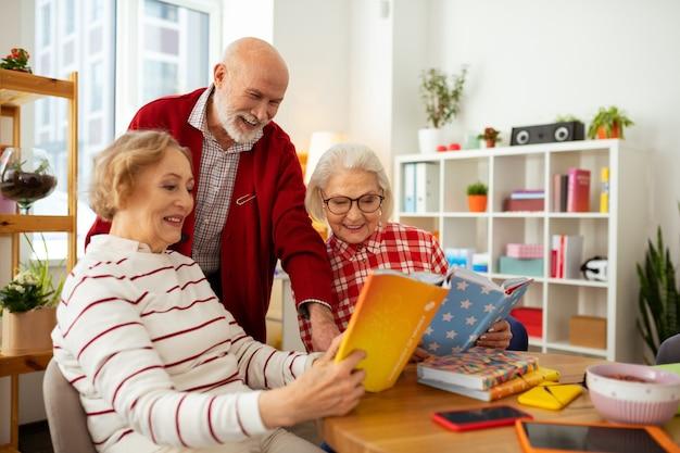 Regardez ici. joyeuses femmes âgées souriant tout en montrant des livres à leur ami