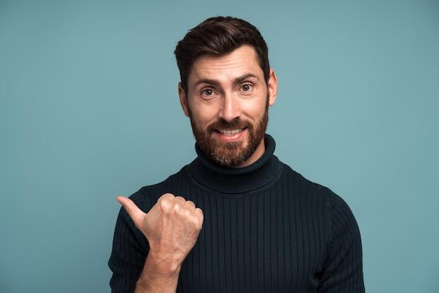 Regardez ici. portrait d'un homme brune sympathique et positif avec une barbe debout et pointant vers la gauche, un espace vide pour le texte, de la publicité. studio intérieur tourné isolé sur fond bleu