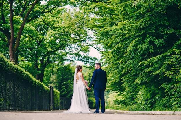 Regardez par derrière un couple de mariage sensuel marchant dans le parc européen