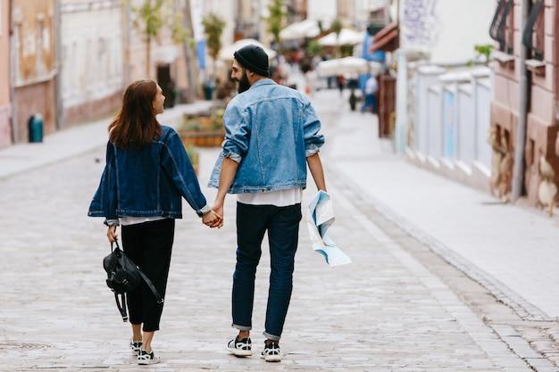 Regardez par derrière le couple de touristes tenant leurs mains ensemble en marchant autour de la ville