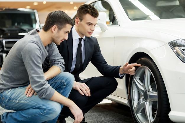Regardez ces pneus ! jeune vendeur de voitures montrant les avantages de la voiture au client