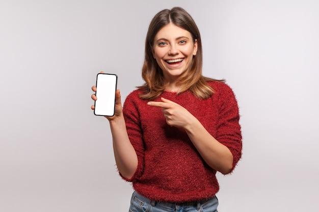 Regardez la publicité mobile! heureuse femme souriante en pull pointant un téléphone portable avec un affichage vide
