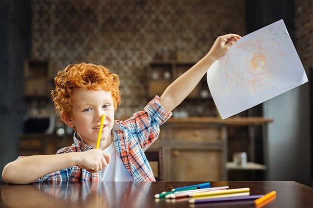 Regardez ce que j'ai dessiné. enfant aux yeux bleus portant une chemise à carreaux touchant son nez avec un crayon coloré assis à une table et montrant son image abstraite dans l'appareil photo.