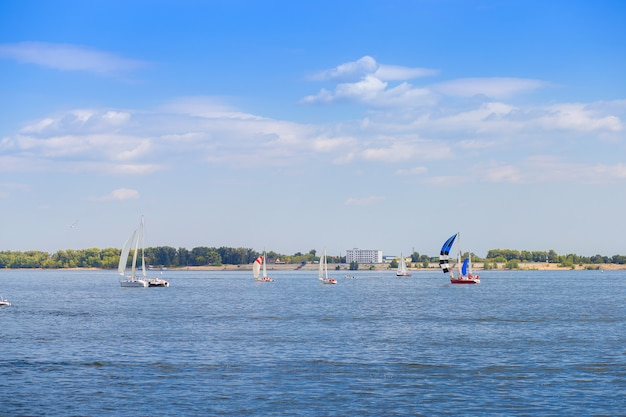 La régate de voile se déroule sur la volga près de la ville de volgograd. de nombreux yachts avec des voiles sur l'eau