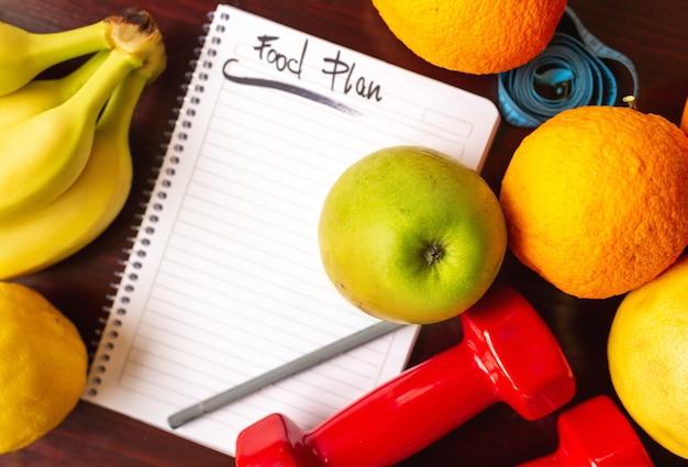 Régime alimentaire. régime alimentaire et fruits et haltères allongés sur une surface en bois