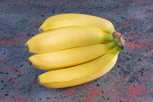 Régime de bananes isolé sur une surface colorée