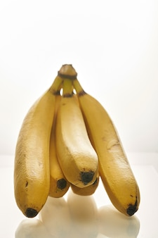 Régime de bananes jaunes mûres sur fond blanc