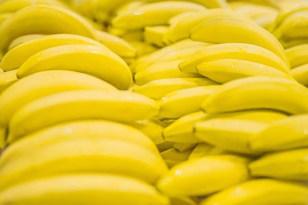 Régime de bananes jaunes en supermarché. frais et sain. faible profondeur de champ, concentrez-vous sur la banane avant.
