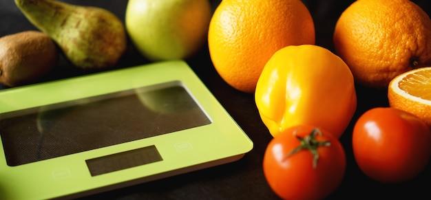 Régime de concept. alimentation saine, échelle de poids de cuisine. légumes et fruits. vue de dessus gros plan sur une surface noire