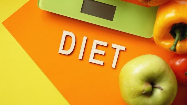 Régime de concept. alimentation saine, échelle de poids de cuisine. légumes et fruits. vue de dessus gros plan sur surface orange