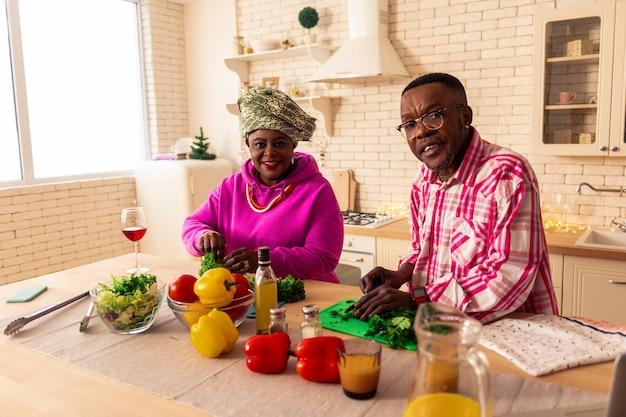 Régime équilibré. beau couple positif debout ensemble dans la cuisine tout en préparant une salade de légumes ensemble