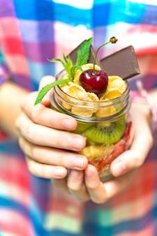 Régime équilibré. fille tenant des flocons d'avoine avec des baies et des fruits
