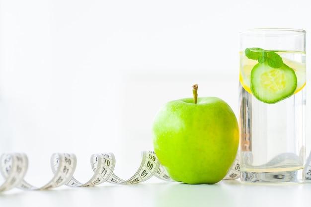 Régime. fitness et concept de régime alimentaire des aliments sains. régime équilibré avec des fruits. fruits frais et eau de verre, ruban à mesurer