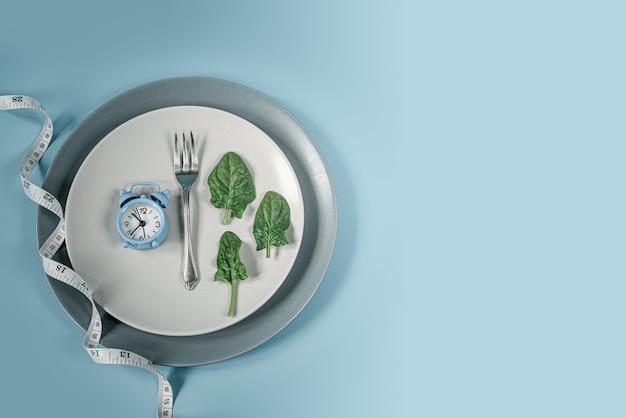 Régime de jeûne intermittent avec horloge bleue, fourchette, feuilles d'épinards et ruban à mesurer sur plaque grise