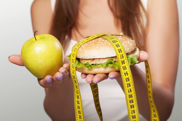 Régime. nourriture nocive et utile. une jeune fille fait un choix soit pour un régime, soit pour un repas. sport. le concept de santé et de beauté. sur fond gris.