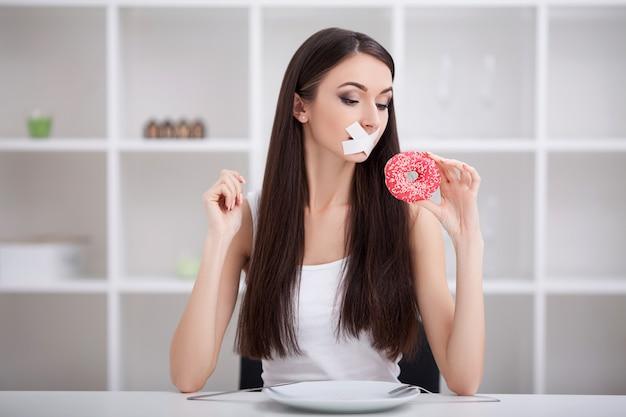 Régime. la nutrition saine et malsaine. le modèle taille plus fait le choix d'une nourriture saine et de fruits en refusant le fast-food et le burger. xxl femme