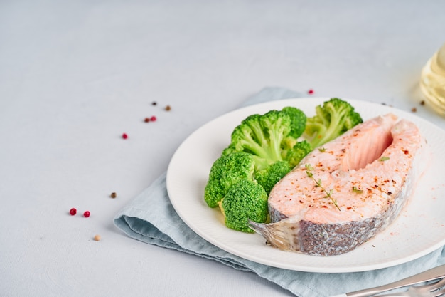 Régime à la vapeur de saumon et brocoli, régime paléo, céto ou fodmap. assiette blanche sur la table bleue, vue latérale