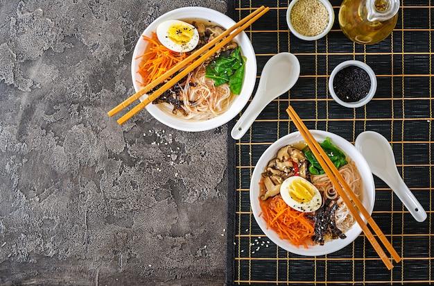 Régime végétarien bol de soupe aux nouilles de champignons shiitake, carotte et œufs durs. nourriture japonaise. vue de dessus. mise à plat