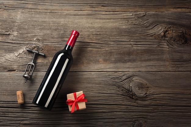 Réglage du dîner de fête avec du vin rouge et un cadeau sur du bois rustique à plat vue.