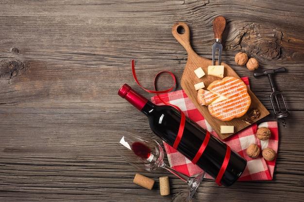 Réglage du dîner de fête avec du vin rouge et du fromage à la crème sur du bois rustique. vue de dessus avec un espace pour vos salutations.
