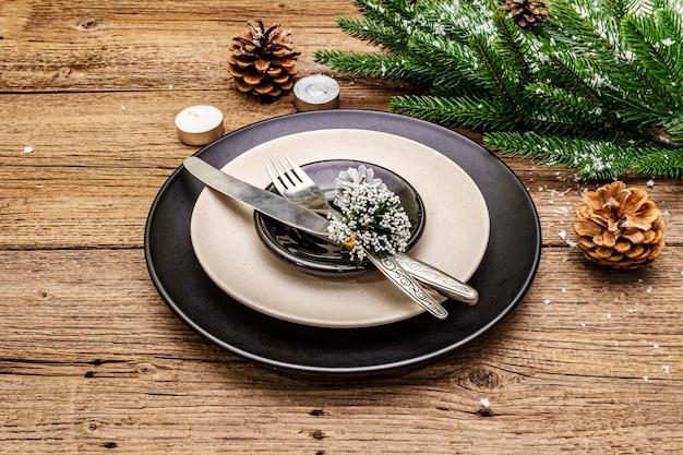 Réglage du lieu du dîner de noël et du nouvel an. branche de sapin à feuilles persistantes, bougies, cônes, assiettes en céramique, fourchette et couteau.