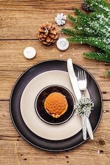 Réglage du lieu du dîner de noël et du nouvel an. collation sucrée, branche de sapin, bougies, cônes, assiettes en céramique, fourchette et couteau.