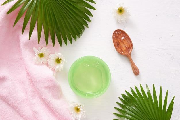 Réglage du spa avec crème cosmétique, gel, sel de bain et feuilles de fougère sur fond de table en bois blanc