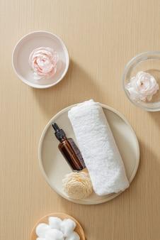 Réglage du spa avec serviette et huile essentielle sur assiette et fleurs sur fond de bois