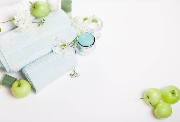 Réglage du spa sur tableau blanc. pommes vertes, serviettes, fleurs de cosmos et hortensias, cosmétiques, bougies. composition de thérapie de station thermale, concept d'été de station thermale. vue de dessus