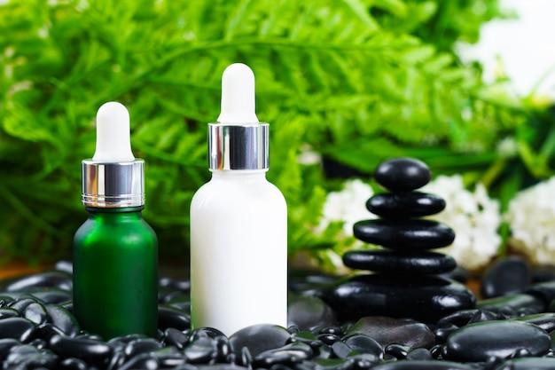 Réglage de massage spa thaïlandais avec bouteille d'huile de sérum compte-gouttes maquette ou huile essentielle sur pierre noire sur fond de congé vert