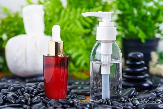 Réglage de massage spa thaïlandais avec compte-gouttes de bouteille d'huile de sérum rouge maquette ou huile essentielle sur pierre noire
