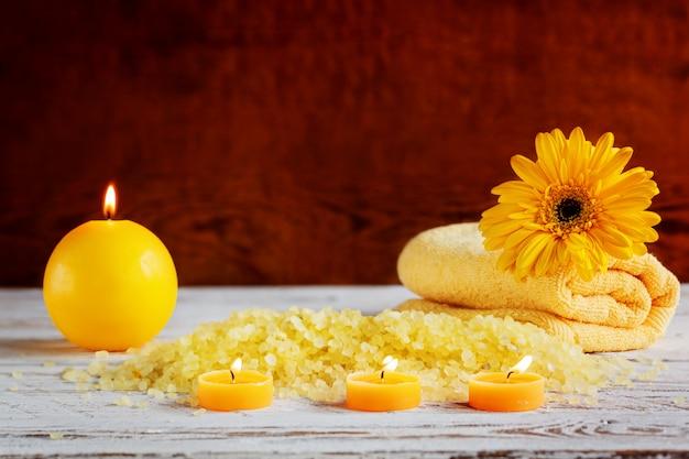 Réglage des produits spa jaune. sel de mer, serviette et bougies sur fond en bois foncé