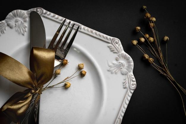 Réglage tabble romantique avec ruban, assiettes, couverts sur fond noir. assiette vide. mise en page de conception de maquette pour votre texte. aime le concept romantique. copiez l'espace. vue de dessus. mise à plat.