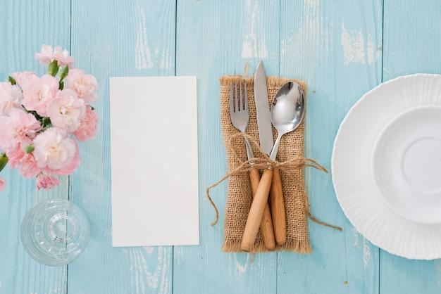 Réglage de la table avec assiette, fourchette et couteau sur fond de bois