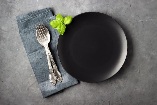 Réglage de la table. assiette noire, couverts, serviette et feuilles de basilic sur béton gris