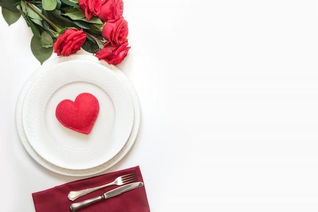 Réglage de la table avec coeur rouge et bouquet de roses rouges. vue d'en-haut. saint valentin.