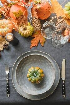 Réglage de la table du jour de thanksgiving avec une assiette vide décorée de citrouilles de feuilles tombées