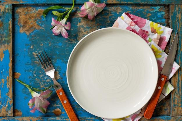 Réglage de la table du printemps ou de la fête des mères couverts et serviette de table sur une table en bois bleu